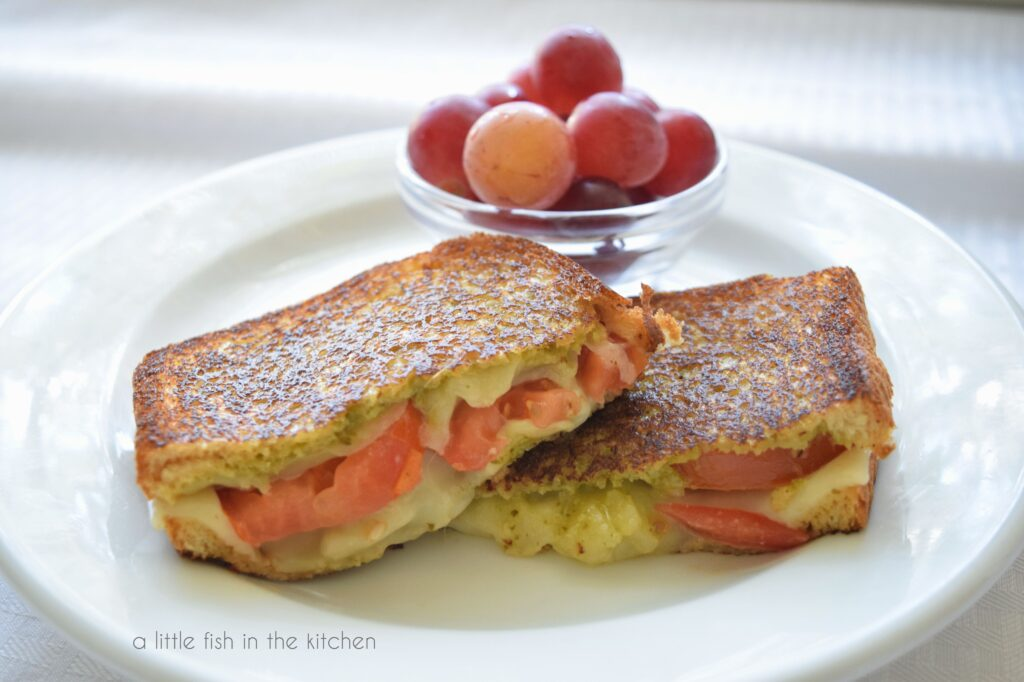 sliced tomato-pesto grilled cheese with grapes on a plate.