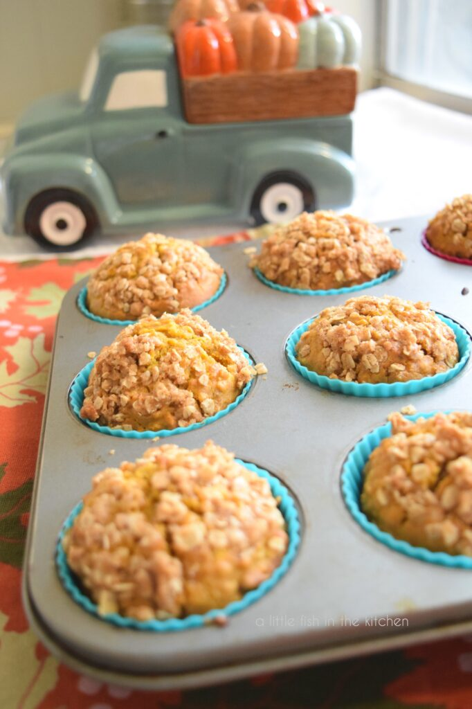 picture of pumpkin oat streusel muffins in a muffin tin with a ceramic teal truck holding pumpkins in it's bed.